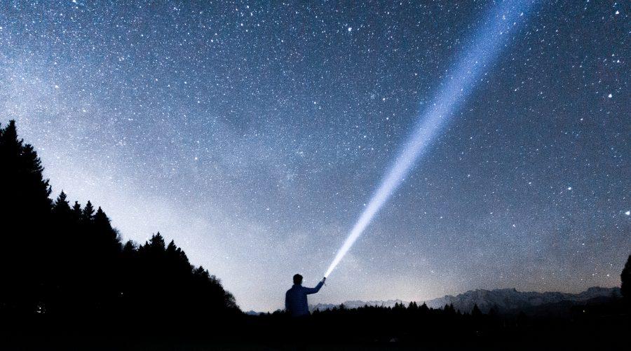 Ragazzo che una torcia illumina un cielo stellato